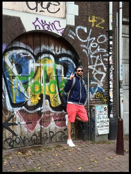 An image of Jeremy Wagshul behind graffiti.