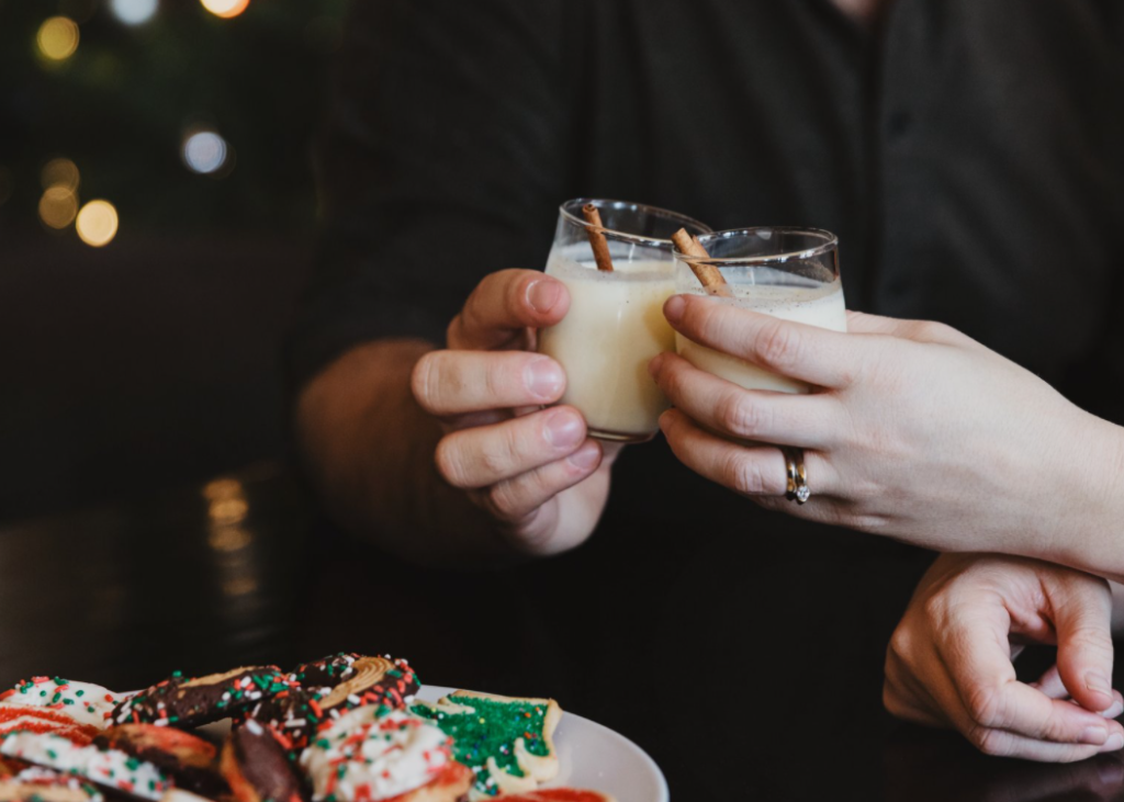 Two people toasting eggnog drinks with holiday cookies to the left.